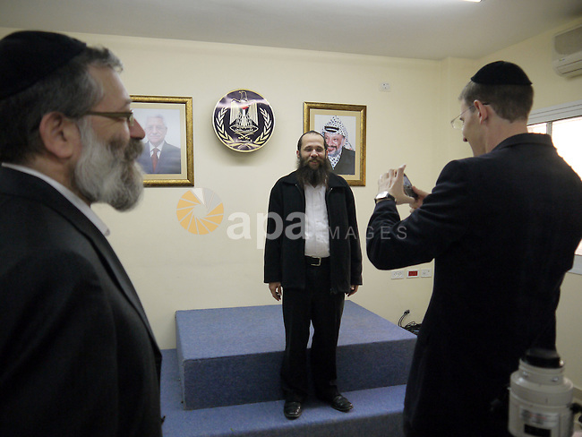 Israeli orthodox Jews pause for a picture with the portraits of late Palestinian leader Yasser Arafat , right, and Palestinian President Mahmoud Abbas prior a meeting with Abbas in the West Bank city of Ramallah, Sunday, Dec. 19, 2010. Palestinian President Mahmoud Abbas hosted dozens of Israeli legislators and peace activists in a rare meeting at his headquarters Sunday and urged them to relay a simple message to the Israeli public, that he is serious about negotiating a peace deal and that the Palestinians will never again resort to violence. Photo by Issam Rimawi