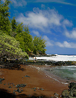 A couple enjoys a secluded seaside walk on the inviting and unique red sand beach of Kaihalulu bay just a stones throw away from the town of Hana.