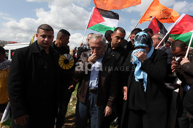Palestinian Prime Minister, Salam Fayyad tries to cover his face to avoid tear gas fired by Israeli soldiers, in the West Bank town of Bilin, on 01 March 2013. The residents of Bilin, west of Ramallah, marked eight years of the village's struggle against the separated wall. Despite the rerouting of the Wall in June 2011, some 1,350 dunams (333 acres) are left on the 'Israeli' side of the Wall and were effectively annexed to the adjacent Jewish settlement of Modi'in Ilit. Photo by Issam Rimawi