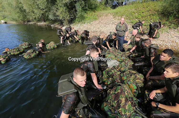 Foto: VidiPhoto<br /> <br /> HETEREN - Op een historische plek langs de Rijn bij Heteren kregen 150 mbo-studenten van diverse ROC's uit Zuid-Nederland dinsdag hun waterdoop. Met de opdracht hun bepakking en 'wapen' droog te houden, moesten ze een 300 meter brede recreatieplas langs de Rijn overzwemmen. Op diezelfde plaats staken bijna 70 jaar geleden Poolse militairen de Rijn over om Britse soldaten te helpen bij de Slag om Arnhem tijdens Operatie Market Garden. De ROC'ers volgen de opleiding Veiligheid en Vakmanschap, waarbij ze maandelijks een week lang een militaire prakttijktraining krijgen. Eenmaal per jaar moeten ze zwemmend met hun bepakking de overkant van een rivier of plas zien te bereiken. Dinsdag gebeurde dat onder toezicht van militairen van de Luchtmobiele Brigade uit Schaarsbergen.