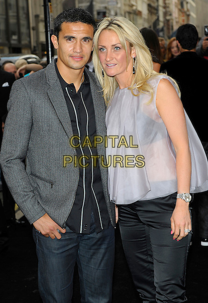 TIM CAHILL & REBEKAH.Vogue Fashion's Night Out - Giorgio Armani Party held at the Emporio Armani store, New Bond Street, London, England, UK.September 8th, 2010.half length grey gray jacket sheer blue top stripe shirt.CAP/CJ.©Chris Joseph/Capital Pictures.