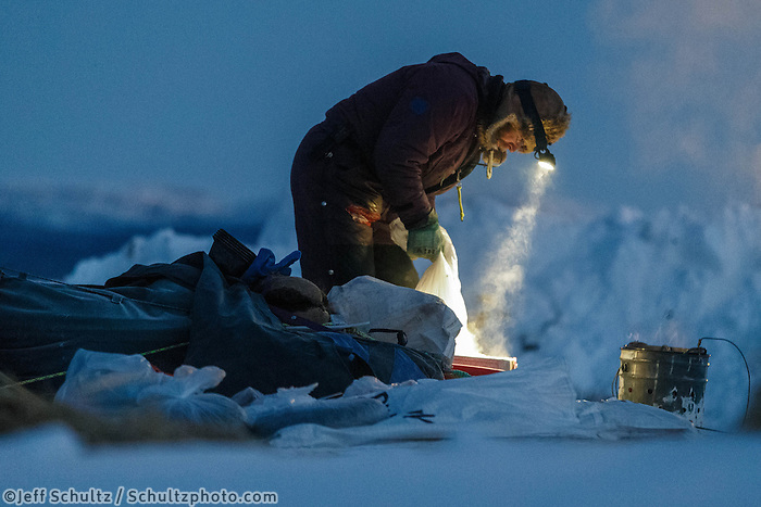 Bob Bundtzen makes dog food in Ruby on Saturday, March 8, during the Iditarod Sled Dog Race 2014.<br /> <br /> PHOTO (c) BY JEFF SCHULTZ/IditarodPhotos.com -- REPRODUCTION PROHIBITED WITHOUT PERMISSION