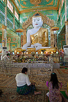 Myanmar, Burma.  Buddha Statue and Worshipers, near Mandalay.  Soon U Ponya Shin Pagoda, Sagaing Hill.
