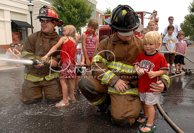 Kids and firefighters participate in a friendly firehose battle during the annual Fourth of July Celebration and community parade in Birkdale Village in Huntersville, NC. Birkdale Village combines the best of shopping, dining, apartments and entertainment venues within a 52-acre mixed-use development.