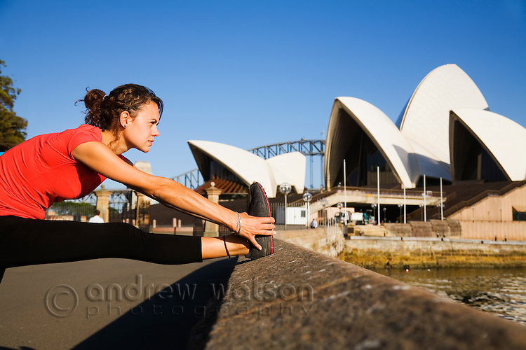 A jogger stretches on the Sydney Harbour waterfront in front of the Opera House.  Sydney, New South Wales, AUSTRALIA