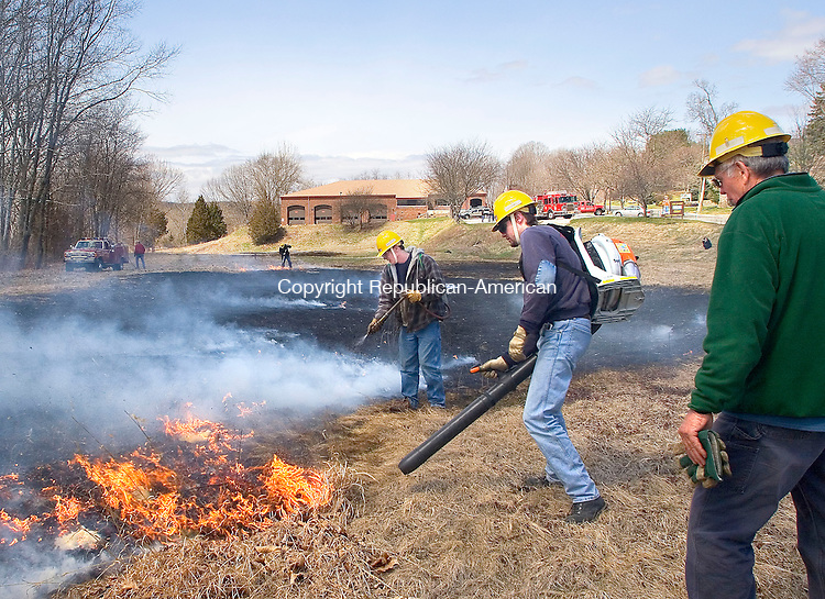 WOODBURY, CT- 14 APRIL 2007-041407JW11.jpg -- Woodbury firefighters Nick Kiessling and David Knapp work to put out a man-made brush fire during a practice session under the watchful eye of Woodbury wildland firefighting instructor Bud Neal. Firefighters use the leafblower to to suppress the advancement of the flames long enough for water to be sprayed down. Jonathan Wilcox Republican-American