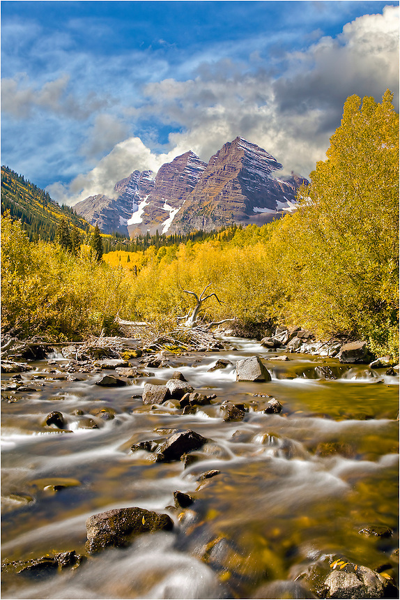 Flowing down from Colorado's high country snows, Maroon Creek runs clean and cold in Autumn. Along the valley, aspen turn gold and the Maroon Bells rise from the beautiful landscape.
