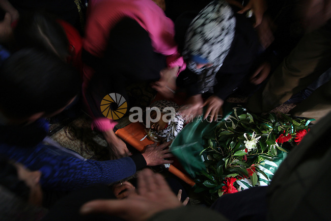 Palestinians carry the body of the 17 year old Samir Awad during his funeral in the West Bank village of Budrus near Ramallah, Tuesday, Jan 15, 2013. The Israeli military shot Awad dead near the West Bank separation barrier on Tuesday, Palestinians said. The Israeli military said he had breached the barrier, which separated soldiers from protesters. Photo by Issam Rimawi