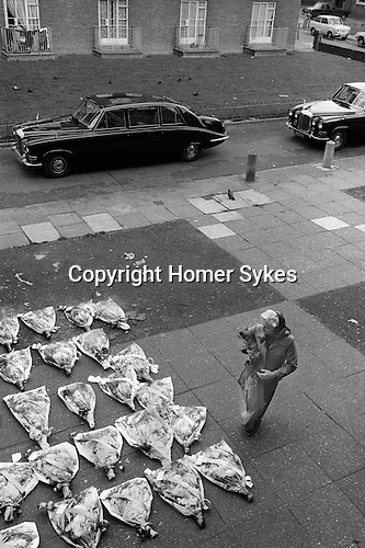 Hoxton east London. Funeral woman bring flowers and tp pay her respect. 1978.<br />