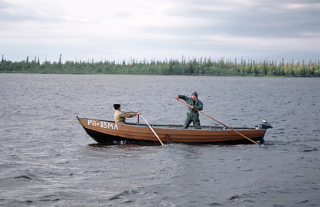 Sami men set out in a wooden boat to check their fishing nets near Lovozero (strong Lake). Kola Peninsula, NW Russia.