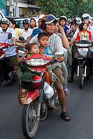 Phnom Penh, Cambodia. Evening rush hour seen from aboard a Tuk Tuk. Kids on motorbikes.