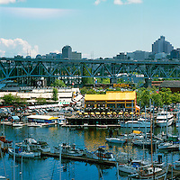 Overlooking Bridges Restaurant and Public Market on Granville Island and Marina in False Creek, Vancouver, British Columbia, Canada, in Summer.  The Granville Street Bridge is over Granville Island.