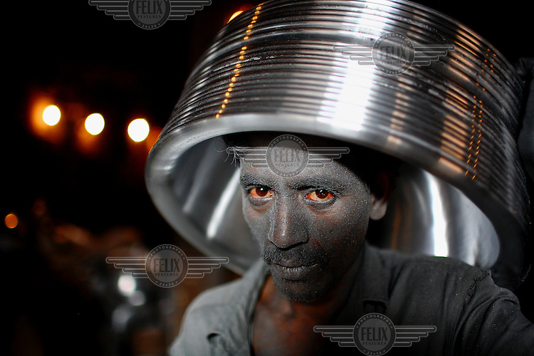 32 year old Anwar, his face speckled with aluminium dust that also irritates and makes his eyes red, carries a part-finished aluminium pot at the factory where he works. He earns around 40 Taka (GBP 0.30) per day.