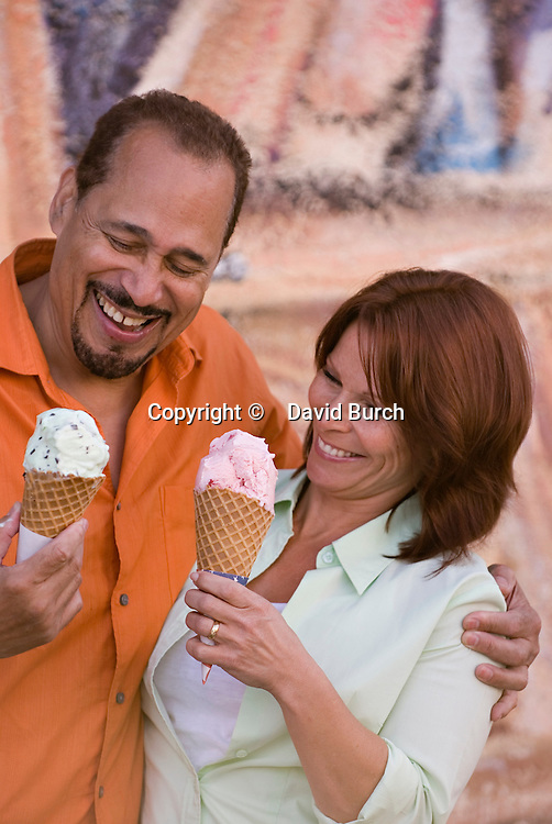 Mature couple holding ice cream cones, smiling