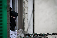 In this Friday, Jul. 19, 2013 photo, a Muslim woman watchs from an appartment window the demonstration of the supporters of the ousted president Mohammed Morsi in the streets nearby Al Rabaa mosque in Nasr City, Cairo. (Photo/Narciso Contreras).