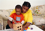 2 year old toddler boy with mother playing with shape sorter toy horizontal