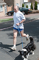 Runner keeping fit by frequent cardiovascular exercise whilst listening to his mp3 player.