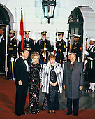 United States President Ronald Reagan, left, and first lady Nancy Reagan, second left, welcome General Secretary of the Central Committee of the Communist Party of the Soviet Union Mikhail Sergeyevich Gorbachev, right, and his wife, Raisa Gorbacheva, right center, to a State Dinner in their honor at the Diplomatic Entrance on the South side of the White House in Washington, DC on December 8, 1987.<br /> Credit: Arnie Sachs / CNP
