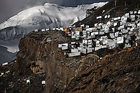 Corrugated metal shacks, homes of gold miners, seen on a steep mountainside under a glacier in La Rinconada, Peru, 3 August 2012. During the last decade, the rising price of the gold has attracted thousands of people to La Rinconada in the Peruvian Andes. At 5300 metres above sea level, nearly 50.000 people work in the gold mines and live in the nearby colonies without running water, sewage system or heating service. Although the work in the mines is very dangerous (falling rocks, poisonous gases and a shifting glacier), the majority of miners have no contract and operate under the cachorreo system - working 30 days without payment and taking the gold they supposedly find the 31st day as the only salary. In spite of a demaged environment, caused by mercury contamination from the mining and the lack of garbage disposal, people continue to flock to the region hoping to find their fortune.