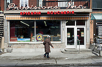 A women walks to an epicerie boucherie (grocery & butcher shop) on avenue Cartier in Quebec city March 16, 2009.