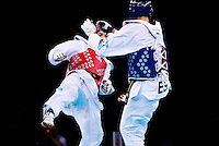 04 DEC 2011 - LONDON, GBR - Aaron Cook (GBR) (on left, in red) aims a kick at Nicolas Garcia (ESP) (on right, in blue) during their men's -80kg category semi final contest at the London International Taekwondo Invitational and 2012 Olympic Games test event at the ExCel Exhibition Centre in London, Great Britain .(PHOTO (C) NIGEL FARROW)
