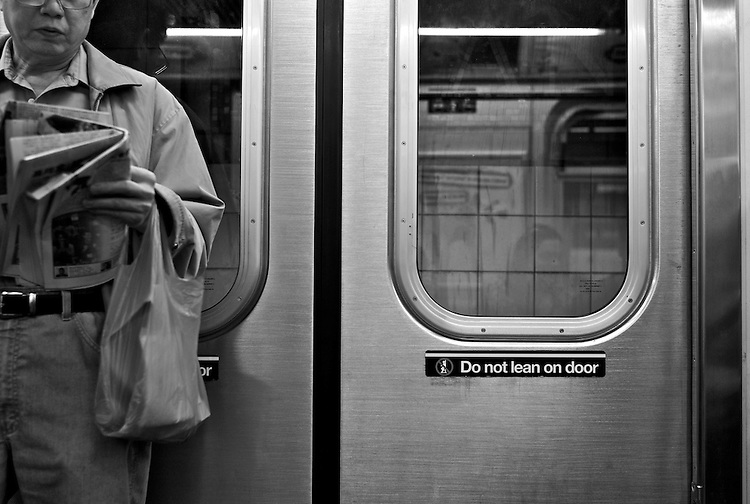 Street shooting with Leica M8. New York City (Manhattan, USA).  Do not lean on door scene in the New York subway.