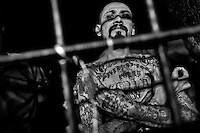 A local gang leader (palabrero) of the Mara Salvatrucha gang shows a hand sign, representing his gang, in the cell of a detention center in San Salvador, El Salvador, 20 February 2014. During the last two decades, Central America has become the deadliest region in the world that is not at war. According to the UN statistics, more people per capita were killed in El Salvador than in Iraq, in recent years. Due to the criminal activities of Mara Salvatrucha (MS-13) and 18th Street Gang (M-18), the two major street gangs in El Salvador, the country has fallen into the spiral of fear, violence and death. Thousands of Mara gang members, both on the streets or in the overcrowded prisons, organize and run extortions, distribution of drugs and kidnappings. Tattooed armed young men, mainly from the poorest neighborhoods, fight unmerciful turf battles with their coevals from the rival gang, balancing between life and death every day. Twenty years after the devastating civil war, a social war has paralyzed the nation of El Salvador.