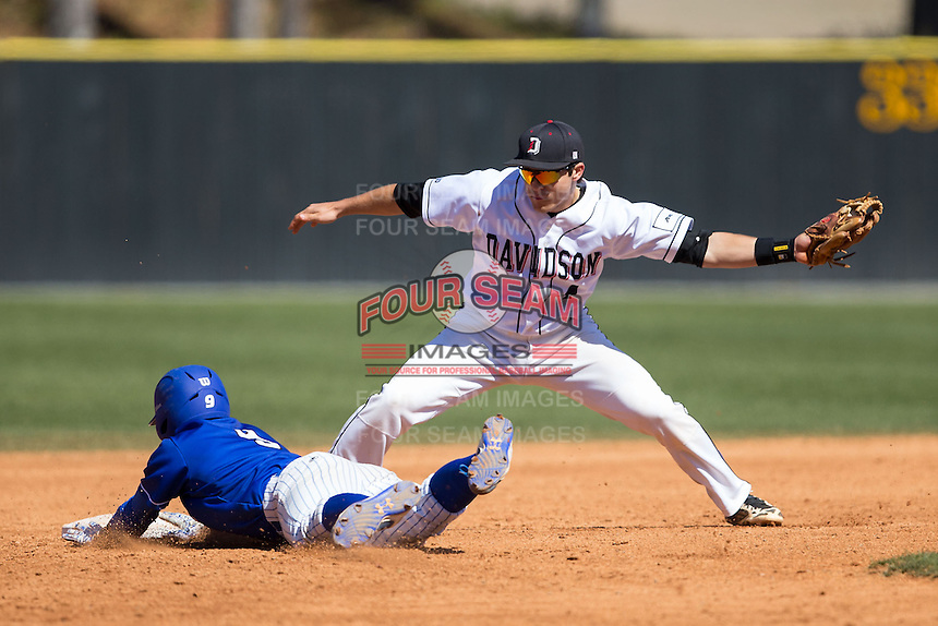 Alex King (9) of the Saint Louis Billikens dives back into second base before Davidson Wildcats shortstop Alec Acosta (4) can apply a tag at Wilson Field on March 28, 2015 in Davidson, North Carolina. (Brian Westerholt/Four Seam Images)