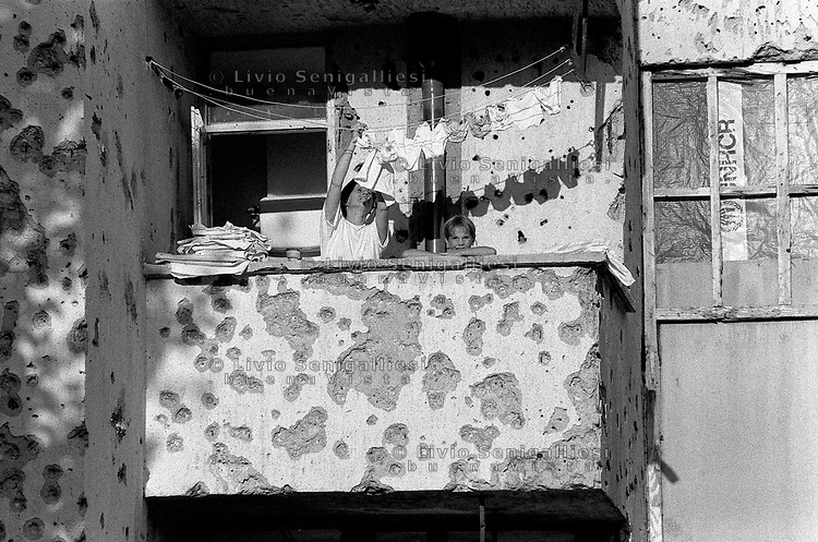 Mostar / Bosnia Erzegovina 1994<br /> Scena di vita quotidiana durante la guerra. Una donna stende i panni sul balcone durante un breve cessate il fuoco. La famiglia ritratta nella fotografia viveva in una casa posta lungo il boulevard, la strada del centro di Mostar diventata prima linea.<br /> Scene of daily life during the war. A woman drys the clothes on the balcony during a brief cease-fire. The family portrayed in the photograph lived in a house located along the boulevard, the street in the center of Mostar became the front line. <br /> Photo Livio Senigalliesi