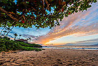 A couple enjoys the sunset while walking the shore of a beach in Wailea, Maui.