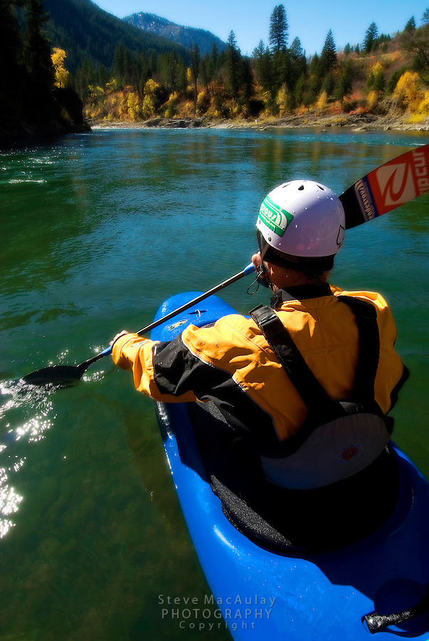 Point of View POV shot of whitewater kayaker in blue kayak and yellow paddle jacket on the green water of the Snake River, Jackson, Wyoming