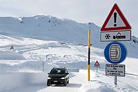Italien, Suedtirol (Alto Adige), Pkw auf dem Jaufenpass (bei 2.000 m) im Winter, Hinweiszeichen fuer Schneeketten, Winterausruestung, Schneeraeumung   Italy, Alto Adige (South Tyrol), pass road Monte Giovo, sign for snow chains, car
