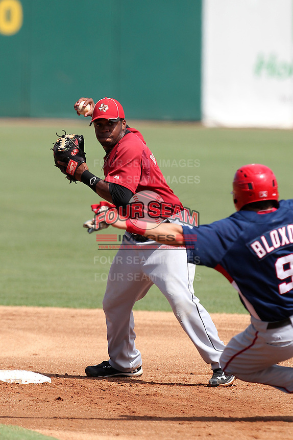 Houston Astros second baseman Delino DeShields #4 turns a double play as Justin Bloxom #9 slides in during an Instructional League game against the Washington Nationals at Osceola County Stadium on September 26, 2011 in Kissimmee, Florida.  (Mike Janes/Four Seam Images)