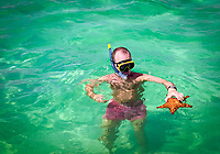 Dominikanische Republik, Mann mit Schnorchel und Taucherbrille steht im Wasser mit Seestern in der Hand | Dominican Republic, man with diving goggles and snorkel standing in water holding a starfish in hands