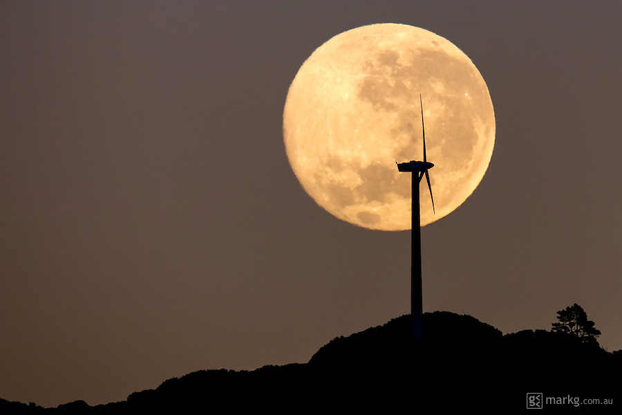 The full moon sets over the Brooklyn wind turbine in Wellington, New Zealand. Wellington is one of the windiest cities in the world, and the Brooklyn wind turbine is Wellington's first and also the oldest operating wind turbine in New Zealand. At 31 meters tall, it is easily seen from most parts of the city. Over the course of a year, the turbine generates the same amount of electricity as 80 homes use in the same period.