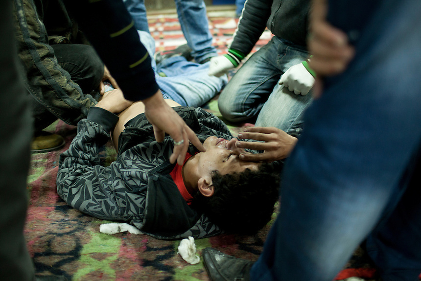 An injured Egyptian protester recieves help from doctors in a makeshift triage unit during clashes near Cairo's Tahrir Square, November 20, 2011. Photo: Ed Giles.