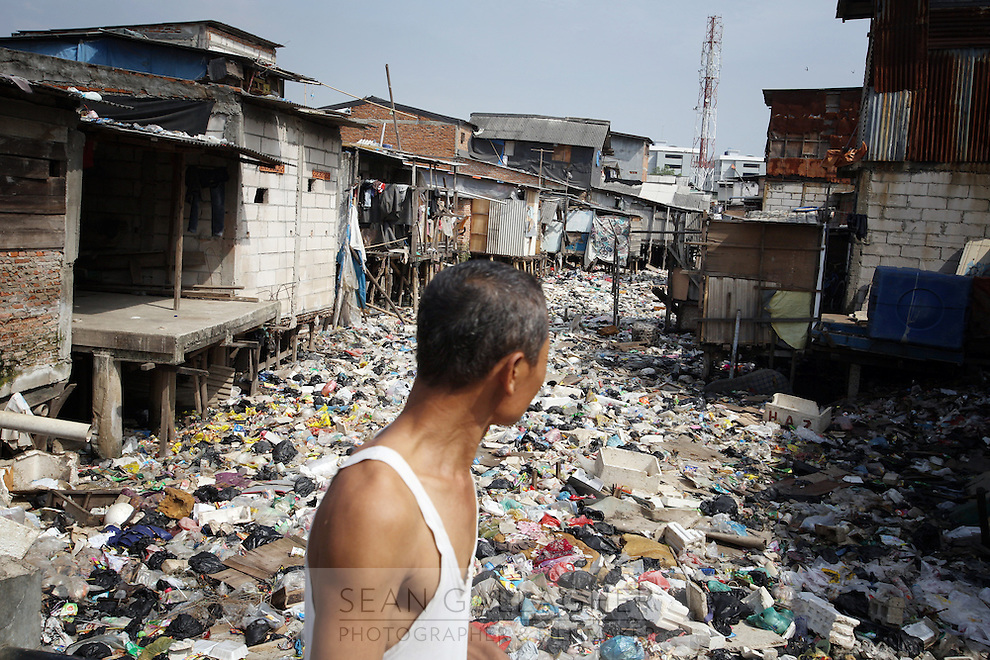 A man walks past a river that has been completely covered with refuse in a slum community in Muara Baru, in north Jakarta. Water pollution is prevalent throughout the city as local residents discard household waste directly into the city's waterways. The floods which ravage the city each January also play a role as they wash large large amounts of refuse into communities such as this, completely blocking the flow of water.