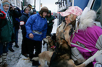 Dee Dee Jonrowe gets kisses from two of her dogs in the staging area during the ceremonial start day of the 2008 Iidtarod Sled Dog Race.