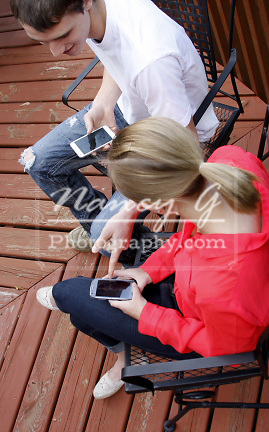 Two teens sitting outside looking at their smart phones