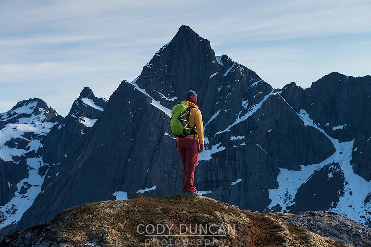 Female hiker looks towards distant mountain from summit of Flakstadtind, Flakstadøy, Lofoten Islands, Norway