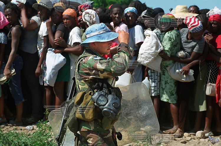 Women queuing for food and relief supplies in the wake of the flood. Food distribution remains difficult, with some aid supplies having been stolen by gangsters. Argentinian soldiers from the United Nations (UN) Stabilization Force have been brought in to provide assistance. .Three weeks after tropical storm Jeanne hit Gonaives parts of the city are still flooded. Over 2700 people were reported dead or missing. Haiti is particularly vulnerable to flooding after heavy rainfall due to intense deforestation.
