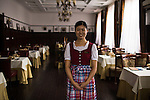 A waitress at a German style beergarden and restaurant located in a building which was formerly used by the German International Club of Qingdao.