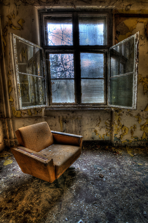 Interior of a decaying old tanks barracks somewhere near Berlin with armchair in room beside open window