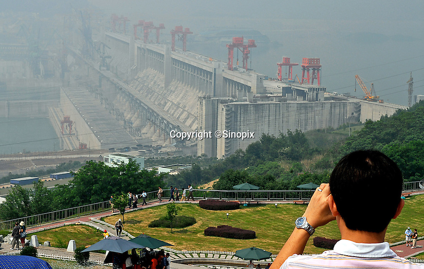 Tourists pose in front of the just completed Three Gorges Dam. The contruction of the Three Gorges Dam and rise in water level of around 100 meters has resulted in the forced relocation of around 1.5 million people but has opened up central China to ocean going vessels and is transforming the economy. The dam will control flooding in the Yangtze river delta and generate hydro-electricity..18 May 2006.photo by richard jones/sinopix