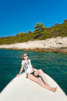 Tourist sunbathing on a boat in the Pakleni Islands, Hvar Island, Dalmacija, Dalmatia, Croatia. This is a photo of a female tourist sunbathing on a boat in the Pakleni Islands near Hvar Island in Dalmacija, Dalmatia, Croatia. One of the best things to do in Croatia, and in particular, Hvar Island in Dalmacija (Dalmatia region of Croatia) is hire a motor boat for the day and explore the Pakleni Islands. It definitely feels like high end luxury travel!