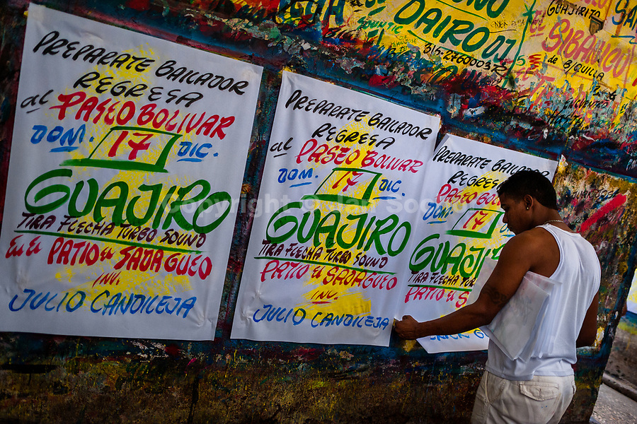 """A Colombian sign painter takes down just-finished music party posters in the sign painting workshop in Cartagena, Colombia, 12 December 2017. Hidden in the dark, narrow alleys of Bazurto market, a group of dozen young men gathered around José Corredor (""""Runner""""), the master painter, produce every day hundreds of hand-painted posters. Although the vast majority of the production is designed for a cheap visual promotion of popular Champeta music parties, held every weekend around the city, Runner and his apprentices also create other graphic design artworks, based on brush lettering technique. Using simple brushes and bright paints, the artisanal workshop keeps the traditional sign painting art alive."""