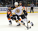 Jan 15, 2009; Uniondale, NY, USA; Boston Bruins leftwing Shawn Thornton (22) battles for the puck against New York Islanders defenseman Chris Campoli at the Nassau Coliseum. Mandatory Credit: Tomasso DeRosa/SportPics