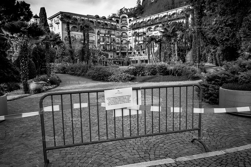 """Switzerland. Canton Ticino. Lugano. A police line and a metal barrier forbid the access to the garden of Grand Hotel Villa Castagnola because of coronavirus (also called Covid-19). Due to the spread of the coronavirus , the Federal Council has categorised the situation in the country as """"extraordinary"""". It has issued a recommendation to all citizens to stay at home, especially the sick and the elderly. From March 16 the government ramped up its response to the widening pandemic, ordering the closure of bars, restaurants, sports facilities and cultural spaces. Only businesses providing essential goods to the population – such as grocery stores, bakeries and pharmacies – are to remain open. 13.04.2020 © 2020 Didier Ruef"""