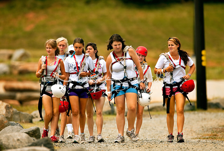 Zip line participants walk back to base after completing the MegaZip zip line run at the US National Whitewater Center (USNWC). The USNWC's zip-lines are part of the facilities high-adventure offerings. The popular outdoor adventure activity lets outdoor enthusiasts be secured into a harness then propelled by gravity along an inclined steel cable. Charlotte, North Carolina's US National Whitewater Center offers multiple zip line courses, which vary in height and distance traveled, as well as one of the largest outdoor climbing facilities in the world. The USNWC is a non-profit outdoor recreation facility open to the public for whitewater rafting, kayaking, canoeing, rappelling, zip lining, mountain biking, hiking, climbing and more. The center opened to the public in 2006.