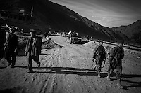 Afghan National Army soldiers and local villagers walk on a main road during a routine patrol in Northern Kunar Province, Afghanistan on Thursday March 25 2010..The Afghan soldier is  from 1st Coi ( Company ), 1st Kandak ( battalion ) 2nd Brigade.